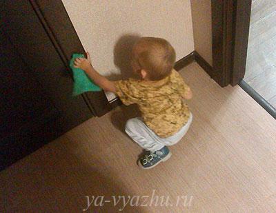 Малыш протирает дверь от пыли